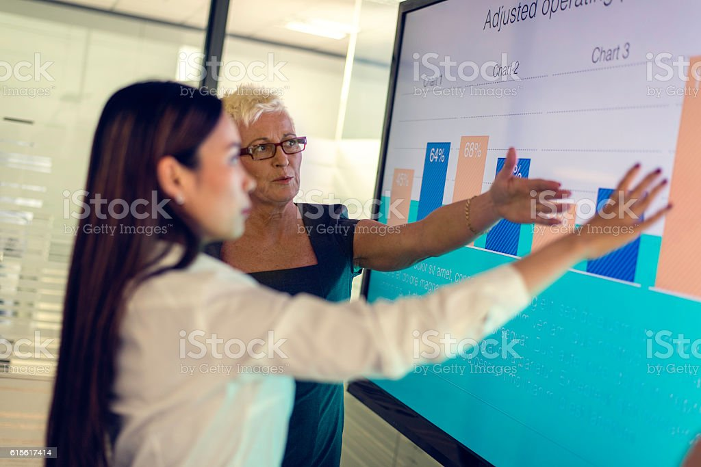 Two women looking at financial graphs stock photo