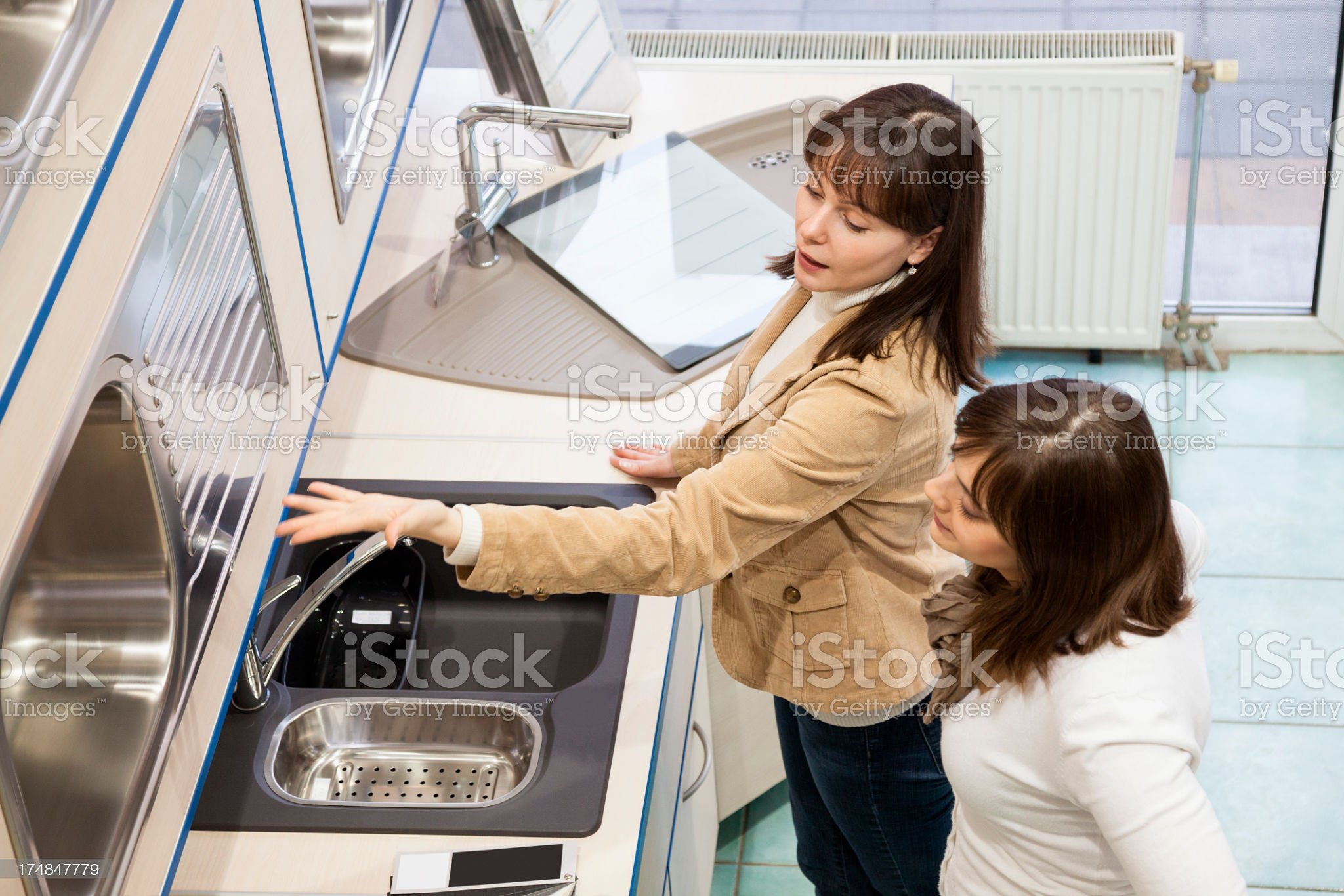 Two women looking at kitchen sinks in a showroom royalty-free stock photo