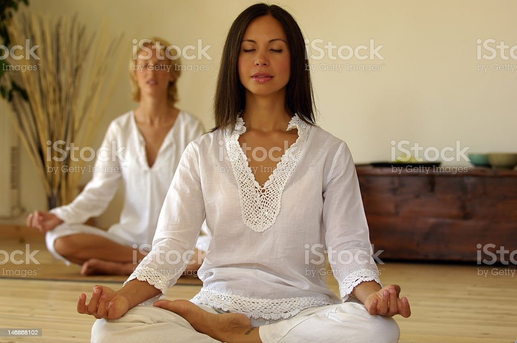Two women meditating stock photo
