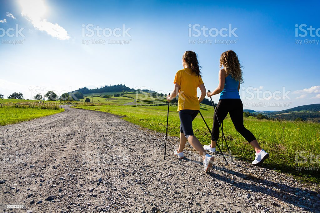 Two women Nordic walking down a gravel road with scenic view stock photo