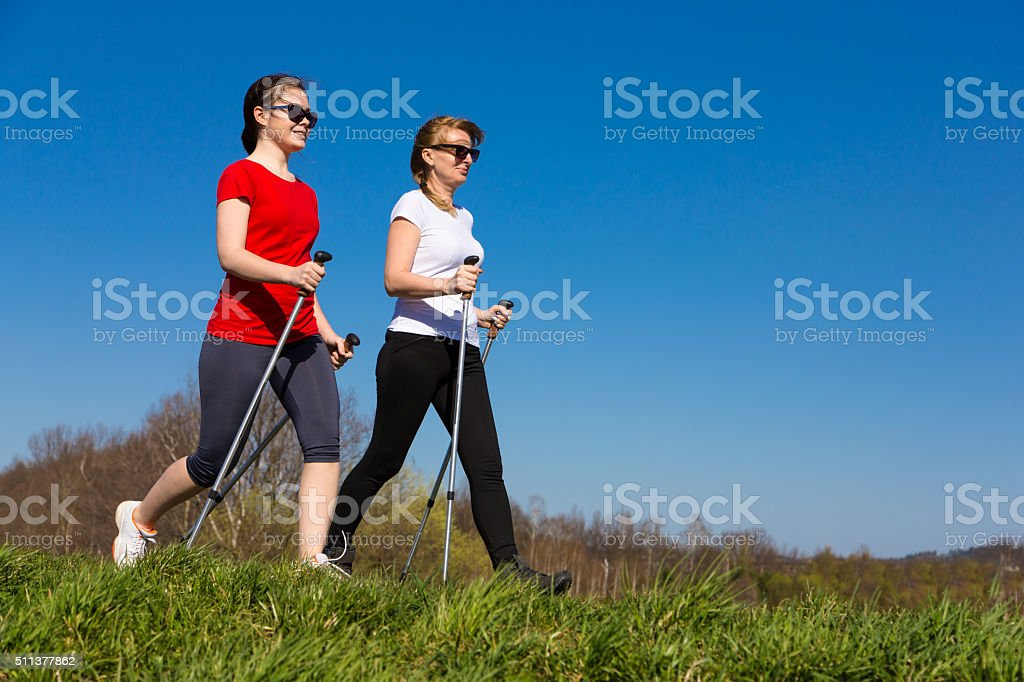 Two women nordic walking stock photo