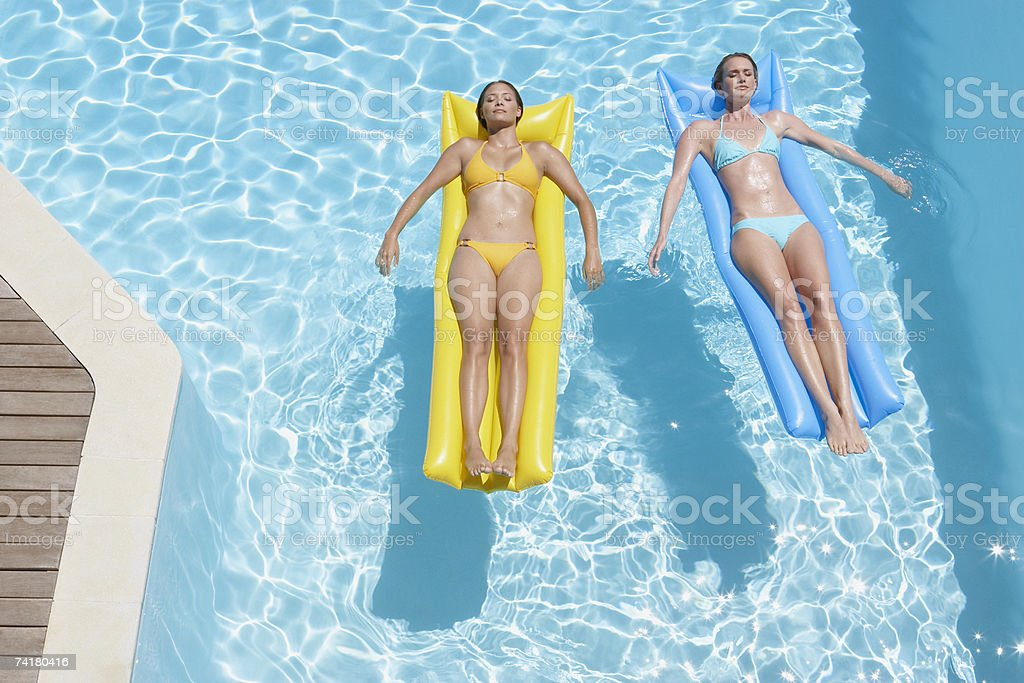 Two women on flotation devices in pool royalty-free stock photo