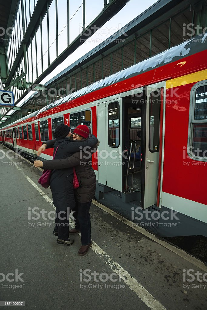 Two women on train station hugging each other royalty-free stock photo