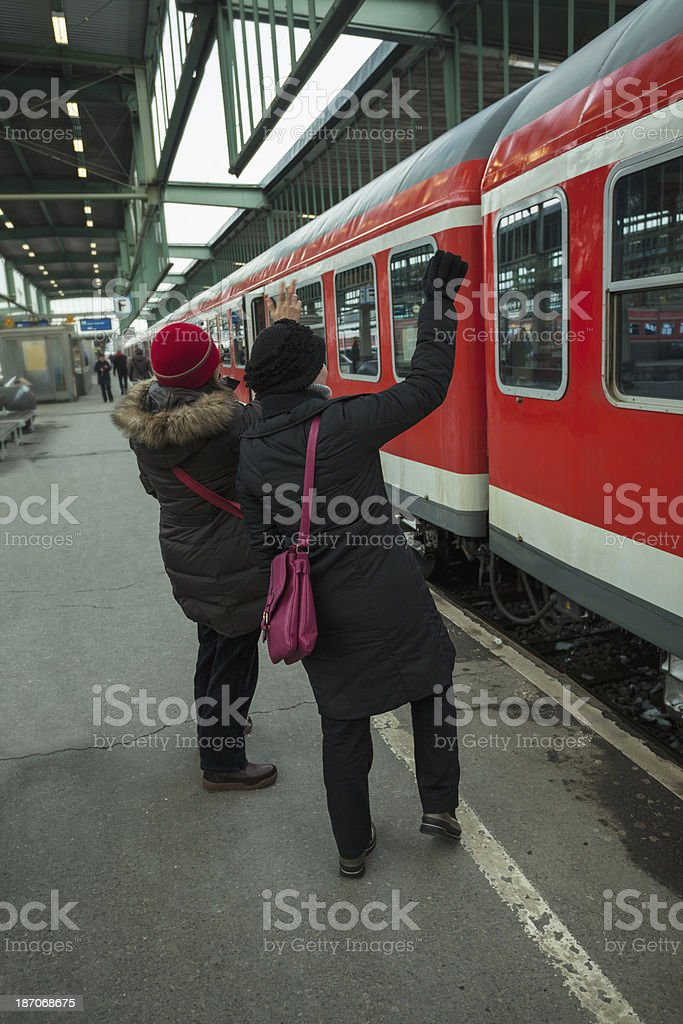 Two women on train station waving to a friend in train royalty-free stock photo