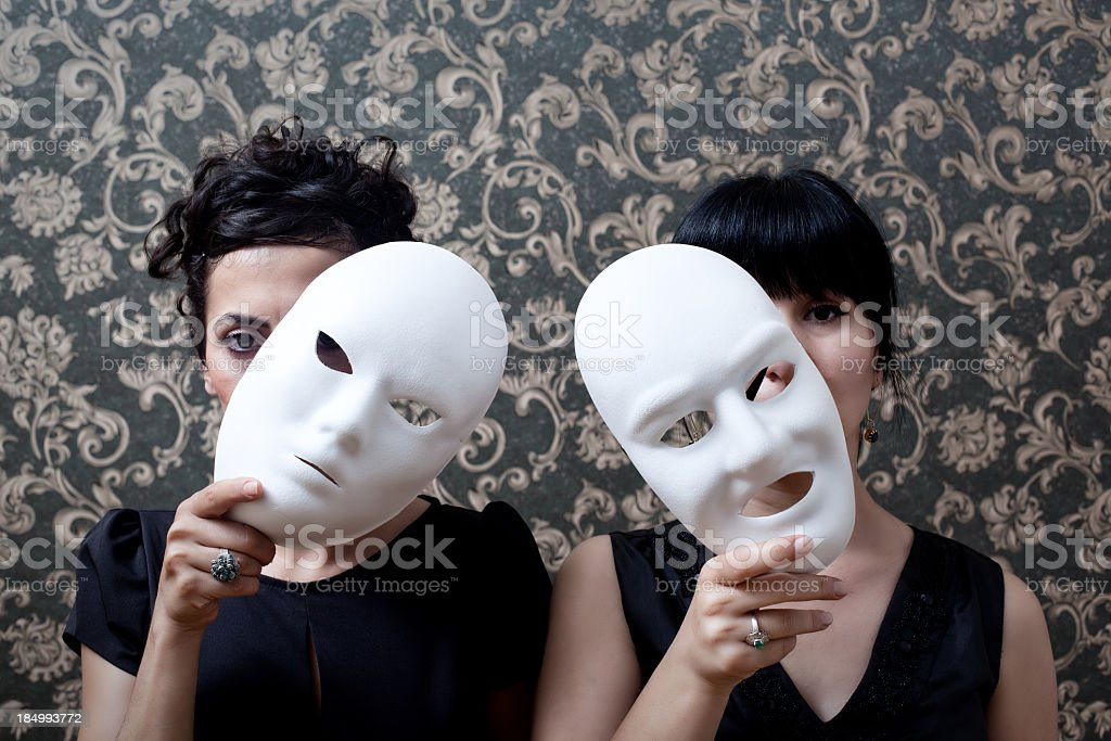 Two women peeking behind mask on wallpaper background stock photo