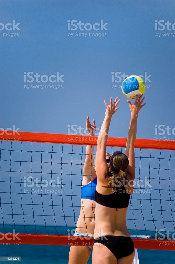 Two women playing beach volleyball stock photo