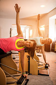 Two women practicing on Pilates stability chairs in health club.
