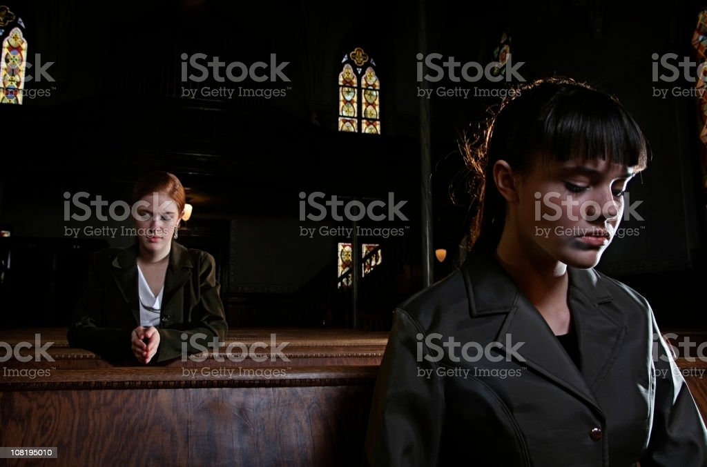 Two Women Praying in an Old Church Cathedral stock photo