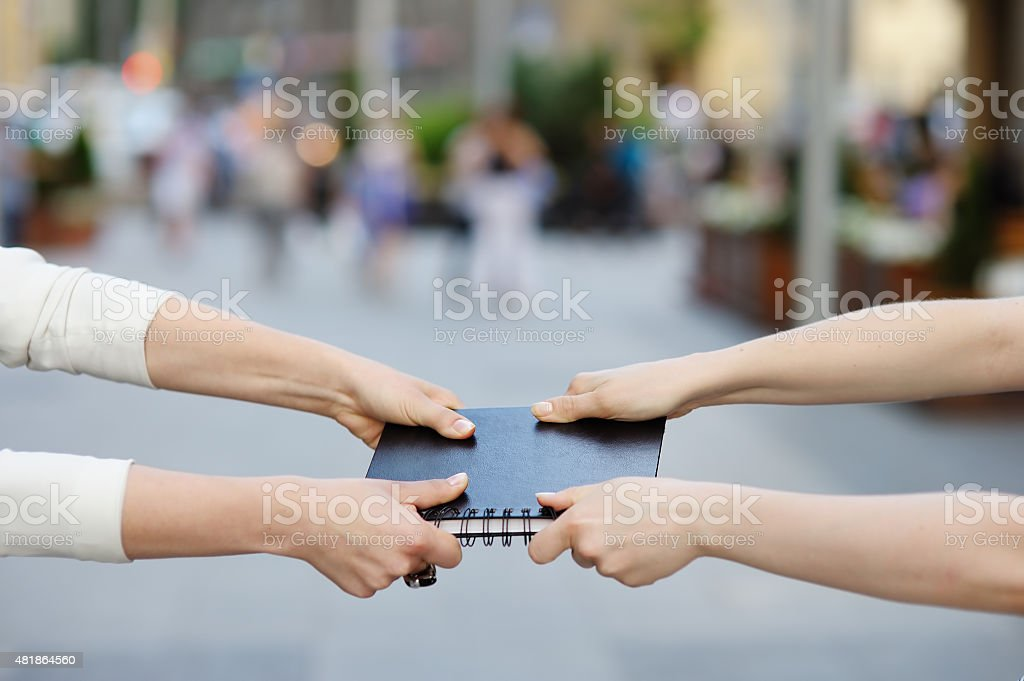 Two women pulls notebook towards each other stock photo
