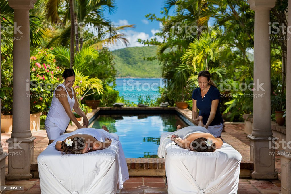 two women receiving massages at a beautiful villa in Caribbean stock photo