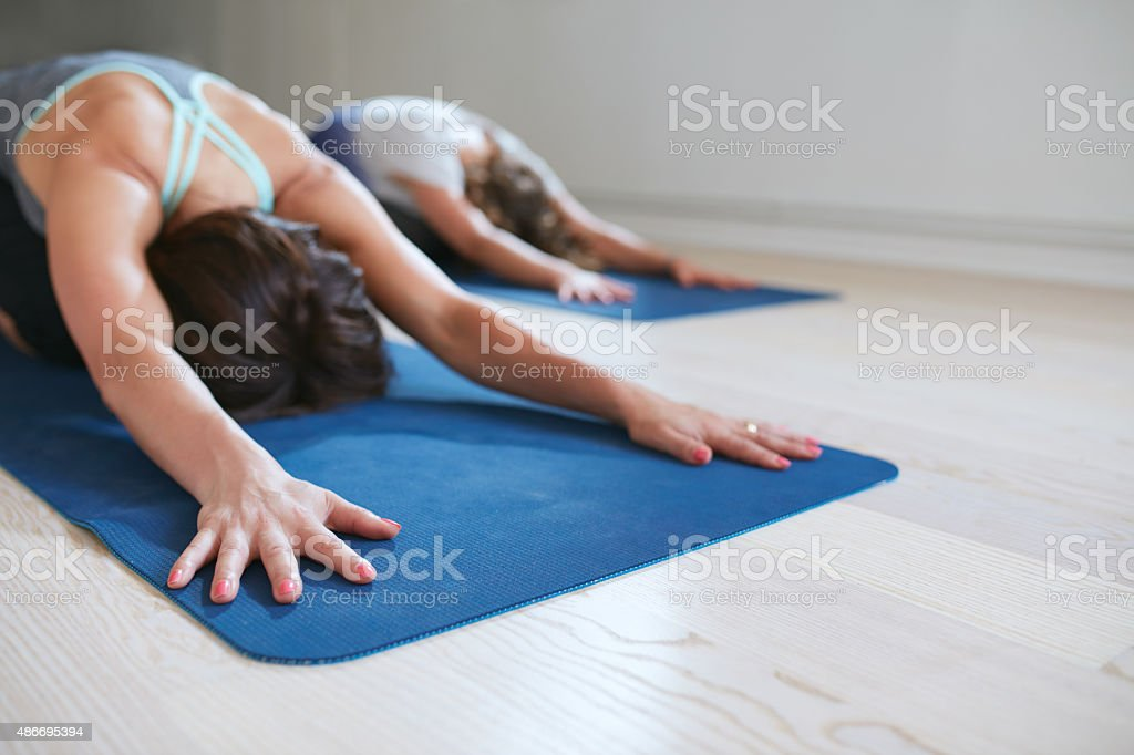 Two women relaxing in child pose doing yoga stock photo