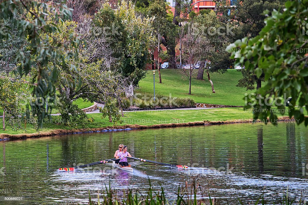 Two women row a double scull on the River Torrens royalty-free stock photo