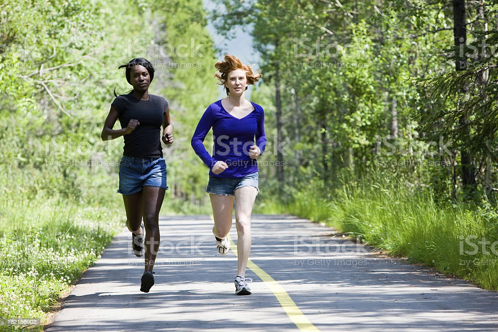 Two Women Running Down A Path In The Woods stock photo