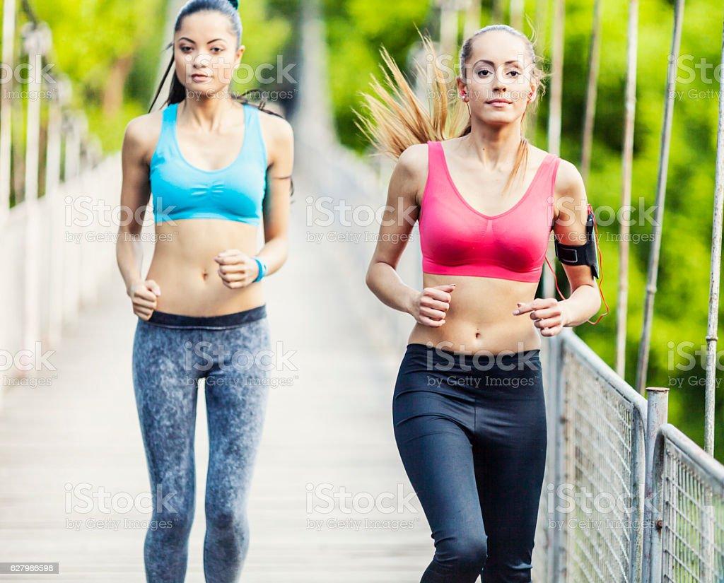 Two women running on rope bridge stock photo