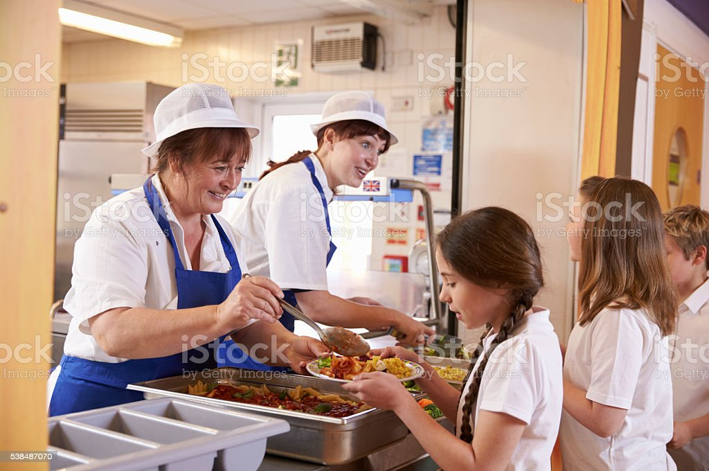 Two women serving food to a girl in a school cafeteria stock photo