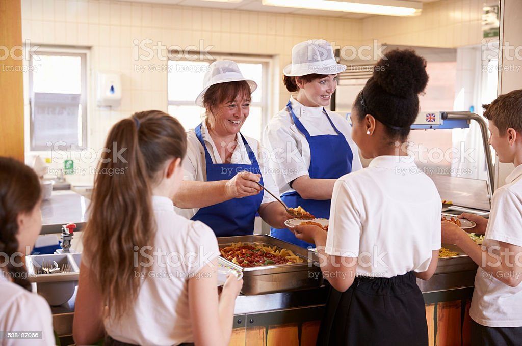 Two women serving kids food in a school cafeteria, stock photo