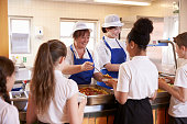 Two women serving kids food in a school cafeteria,