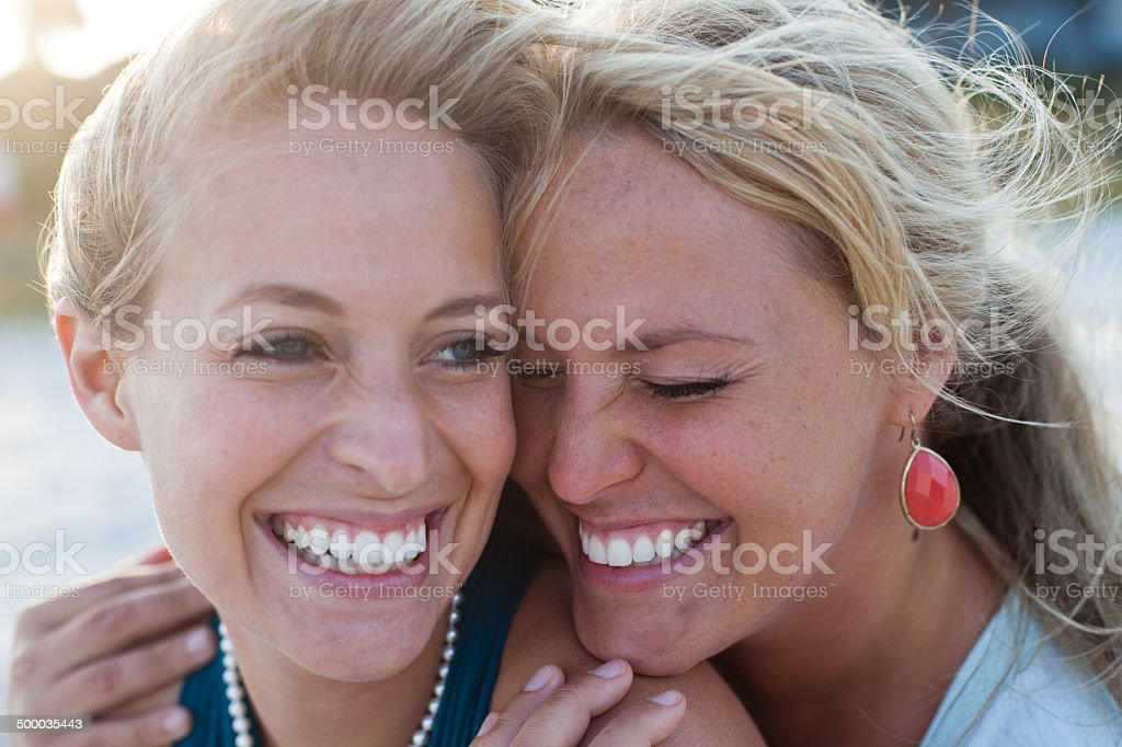 Two women sit on the beach talking and laughing stock photo