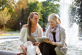two women sitting in front of fountain using digital tablet