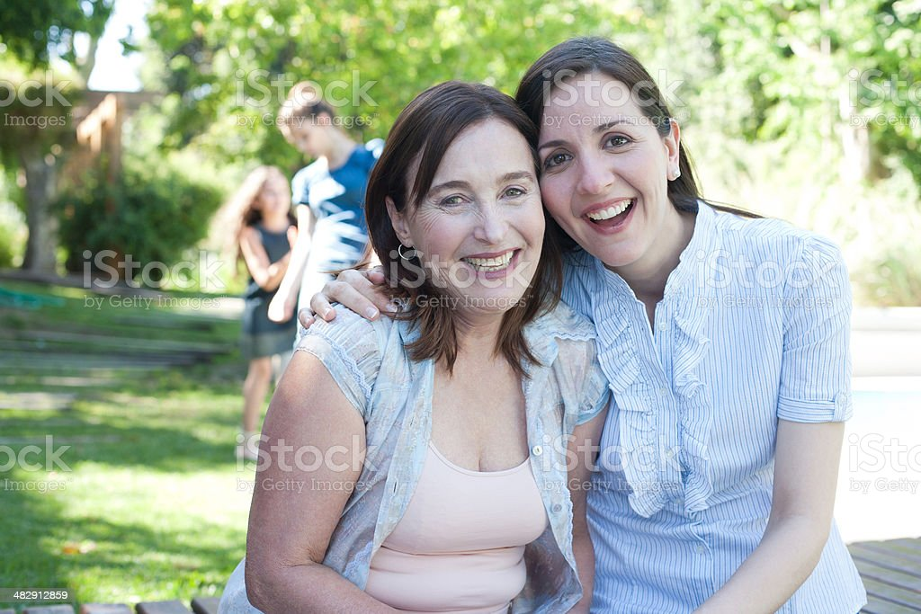 Two women sitting on deck outdoors smiling stock photo