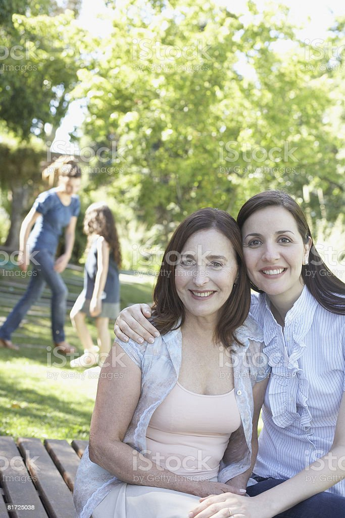 Two women sitting on deck outdoors smiling royalty-free stock photo