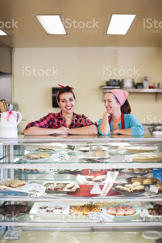 Two women standing at counter of bakery stock photo