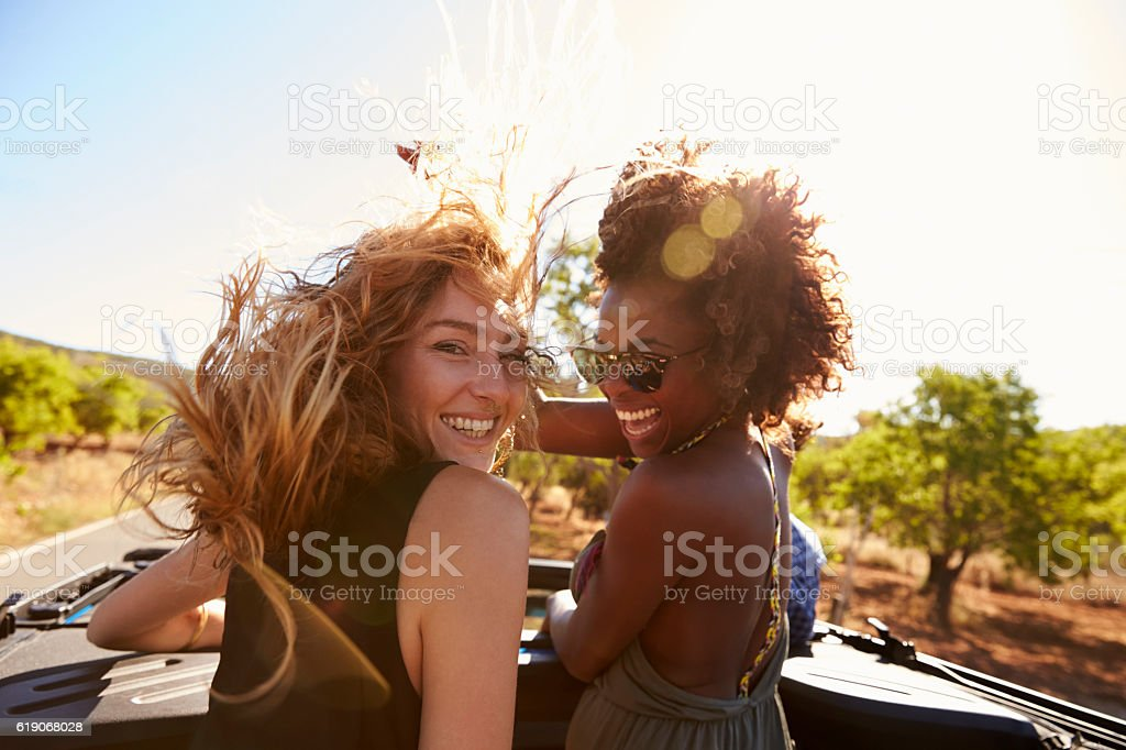 Two women standing in the back of open car turning stock photo