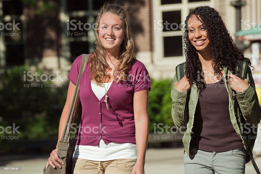 Two Women Student Friends, Teenagers Walking Outdoors on University Campus royalty-free stock photo