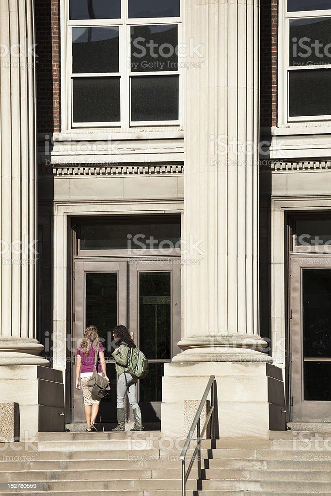 Two Women Students Entering University Academic Hall Roman Column Building royalty-free stock photo