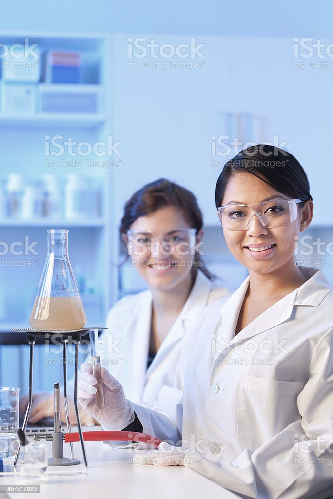 Two Women Students Working Together in Laboratory Vertical royalty-free stock photo