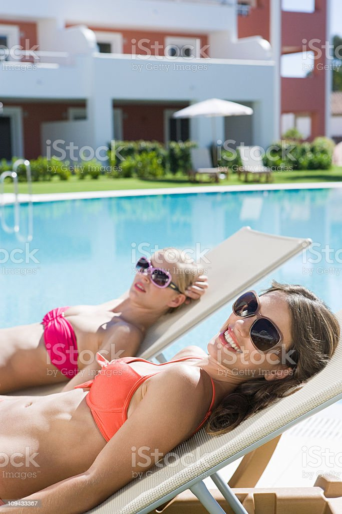 Two women sunbathing on sunloungers at poolside stock photo