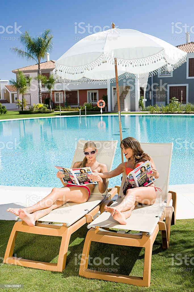 Two women sunbathing on sunloungers reading magazines royalty-free stock photo