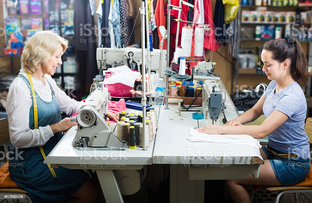 Two women tailors working with sewing machines stock photo