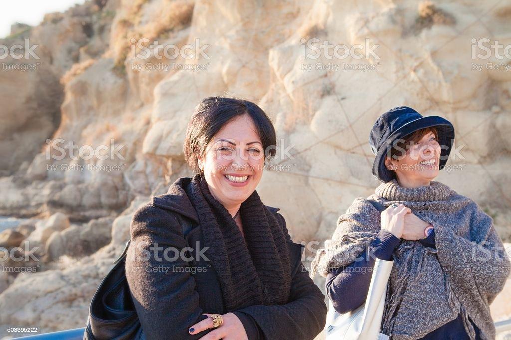 Two Women Talking Outdoors on Seashore stock photo
