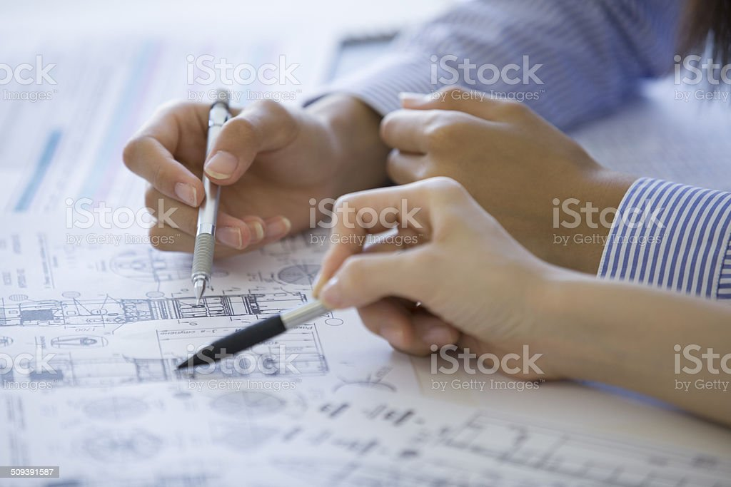 Two women to talk to see the blueprint stock photo