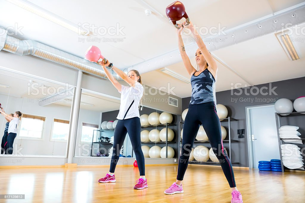 Two women trains with kettlebells at fitness gym stock photo