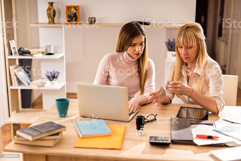 Two women trying to sort out tangled paper clips. stock photo