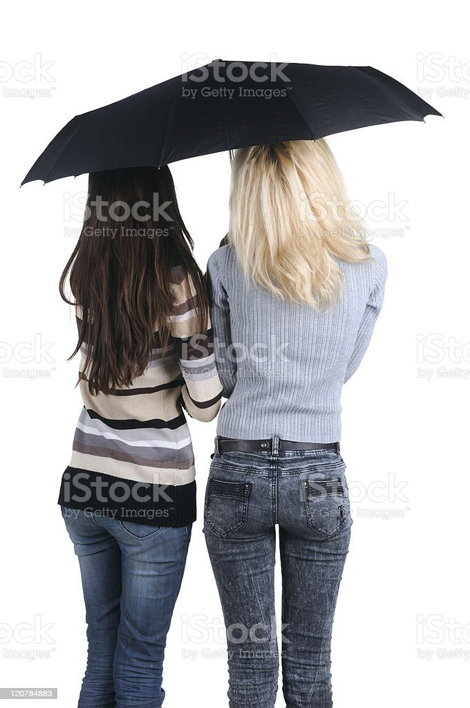 Two women under an umbrella. Rear view. royalty-free stock photo