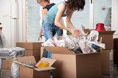 Two women unpacking cardboard boxes