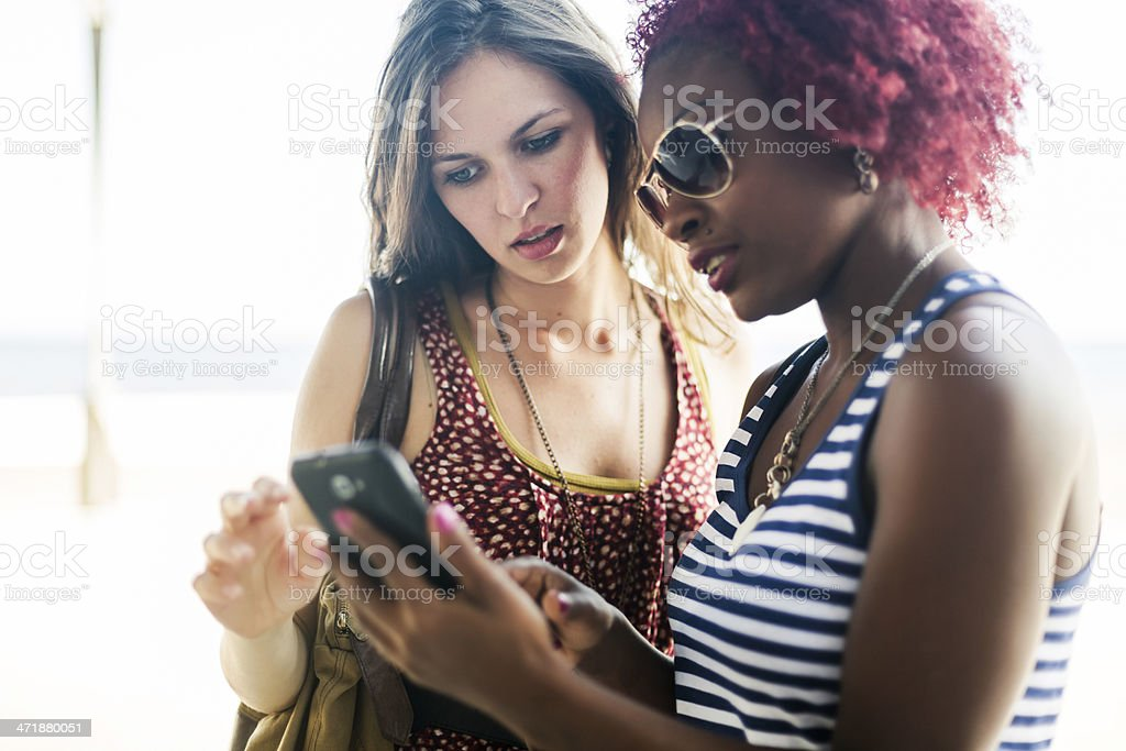Two women using a smartphone royalty-free stock photo
