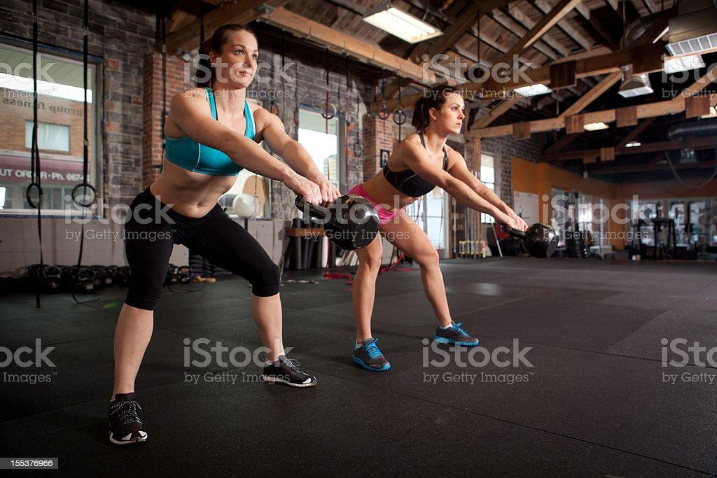 Two women using kettle bells stock photo