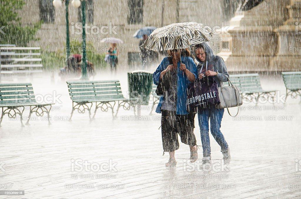 Two Women walk under umbrella during heavy rain. stock photo