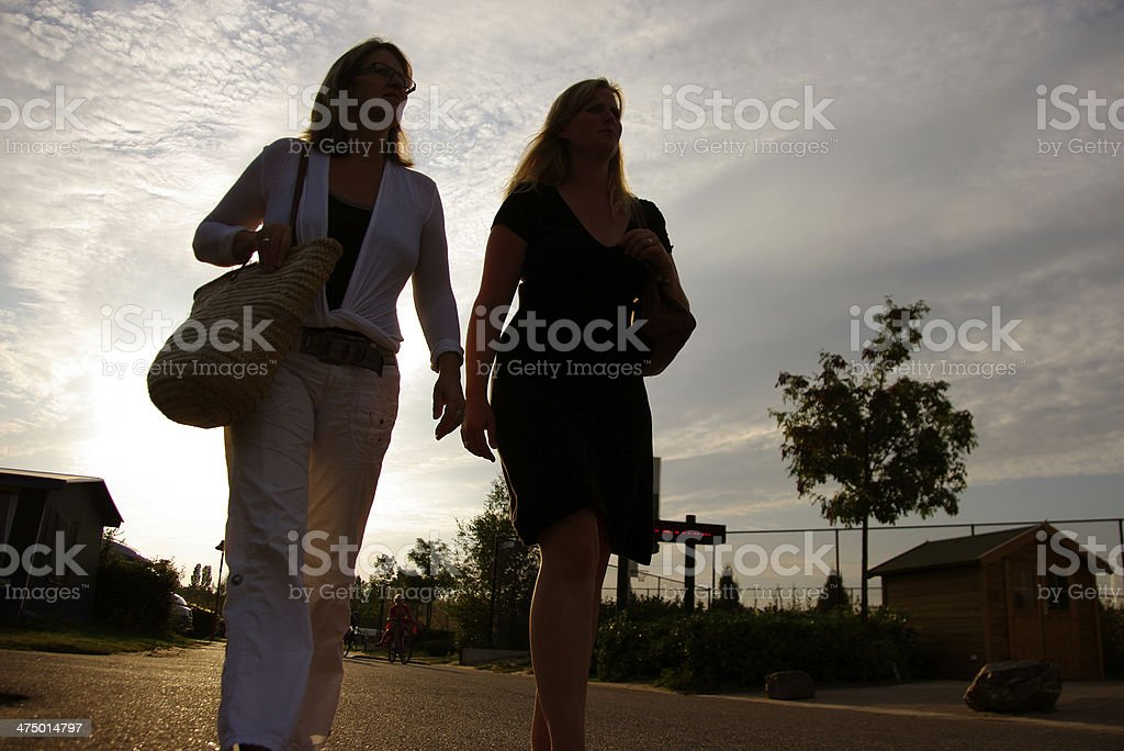 Two women walking at sunset royalty-free stock photo