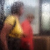 Two women walking behind wet glass