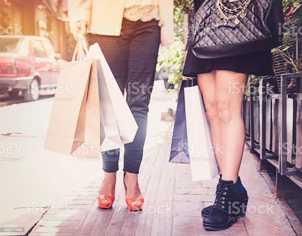 Two Women Walking with Shopping Bags stock photo