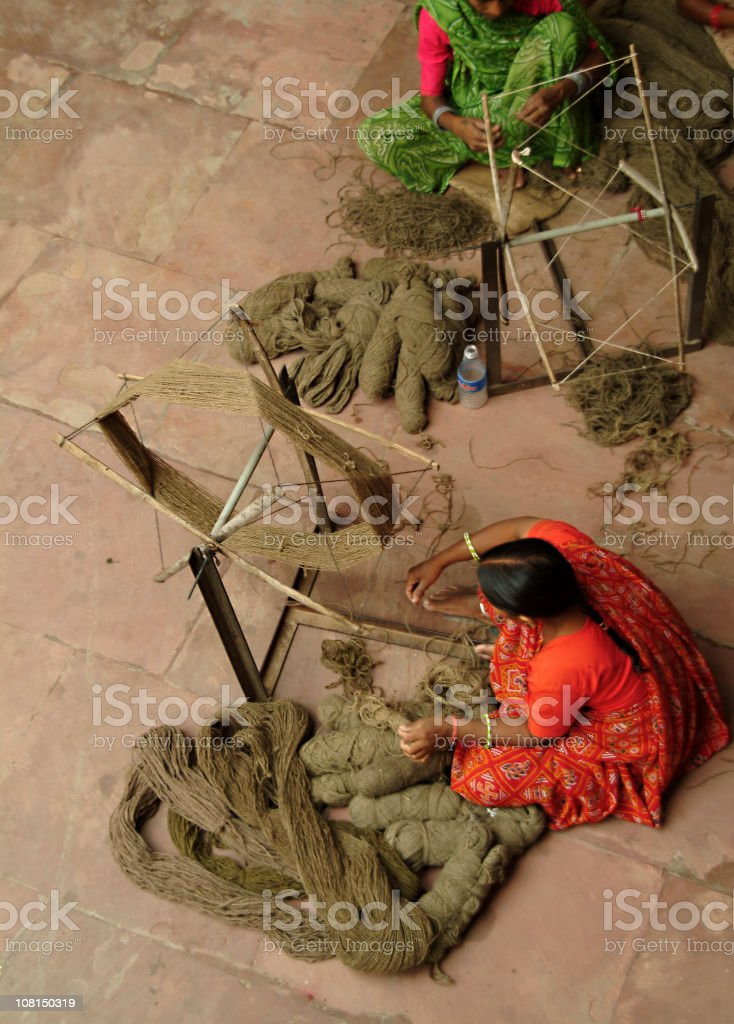 Two Women Wearing Saris and Weaving in Jaipur, India stock photo