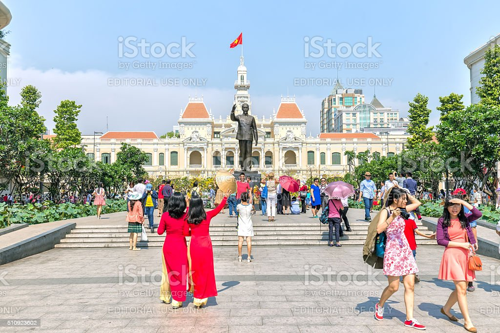 Two women welcome spring before the City People's Committee stock photo
