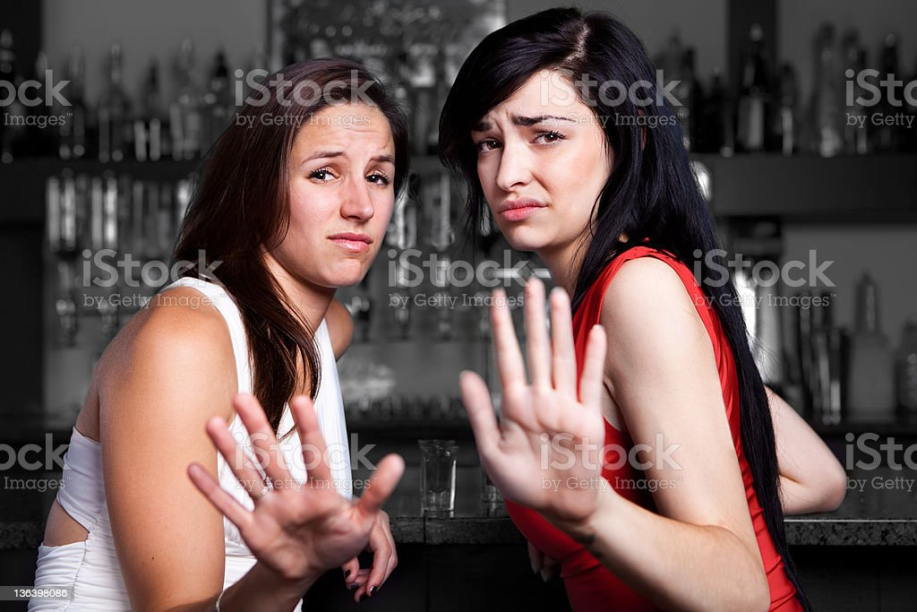 Two women with disgusted faces holding up their palms stock photo