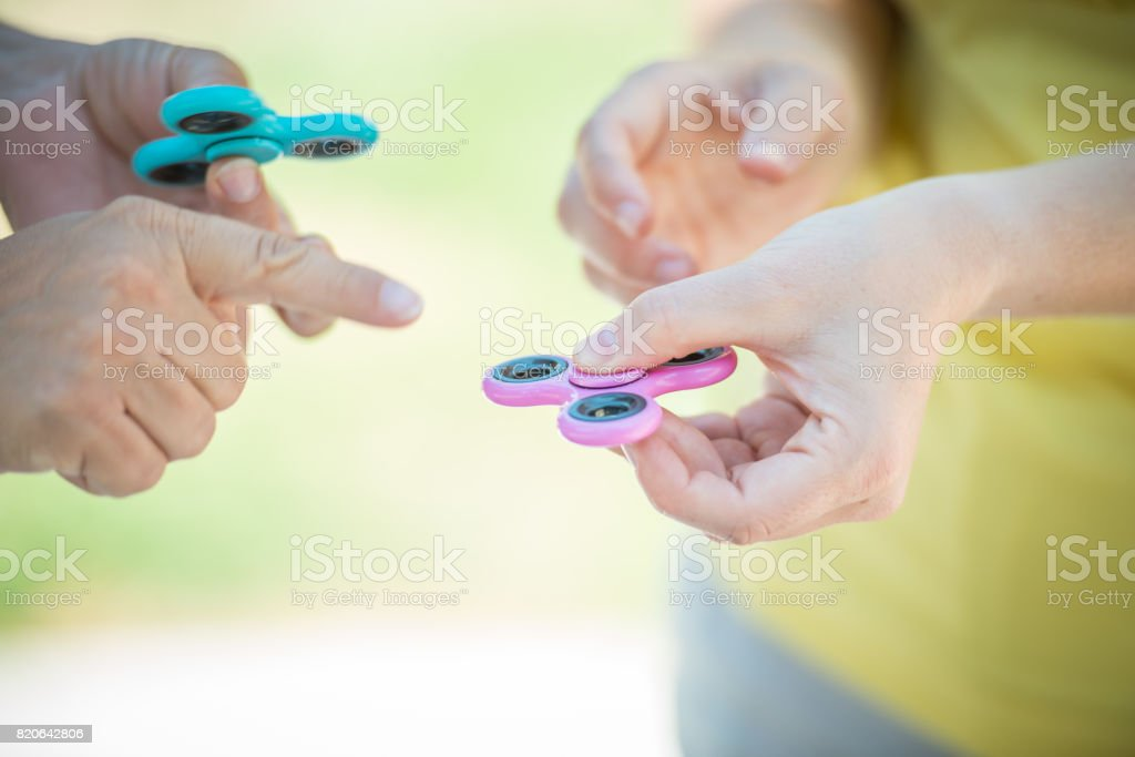 Two women with fidget spinner in her hands close up stock photo