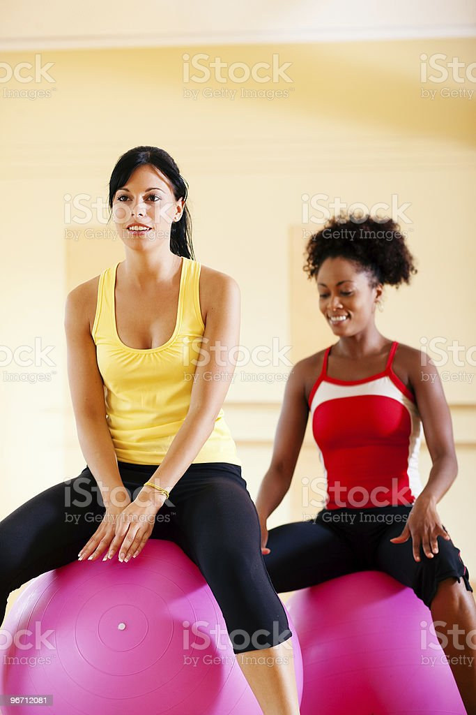 Two women with fitness ball in gym royalty-free stock photo
